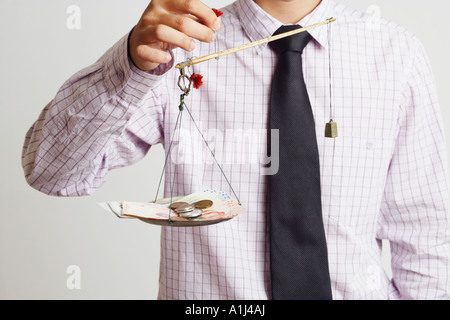 Mid section view of a businessman weighing paper currency with coins on a weighing scale - Stock Photo