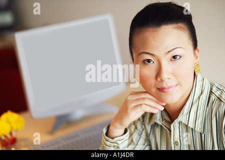 Portrait of a businesswoman thinking with her hand under her chin - Stock Photo