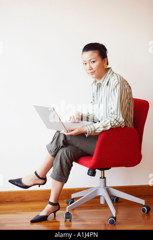 Portrait of a businesswoman sitting in an armchair and using a laptop - Stock Photo
