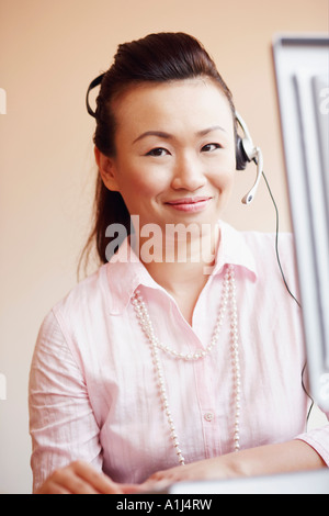 Portrait of a female customer service representative talking on a headset and smiling - Stock Photo