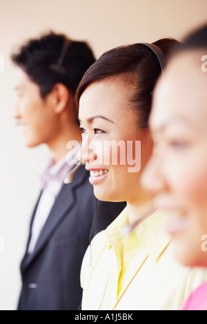 Side profile of a female customer service representative smiling with two colleagues - Stock Photo