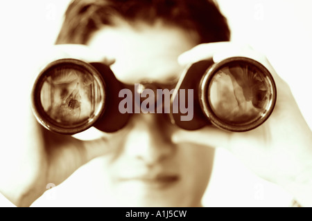 Close-up of a businessman looking through a pair of binoculars - Stock Photo