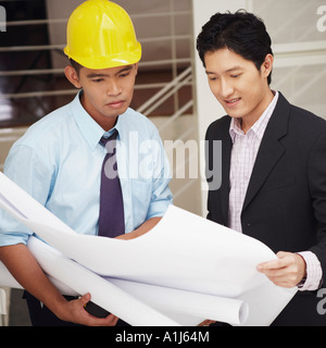 Side profile of a businessman and an architect looking at blueprints Stock Photo