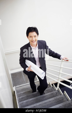 Portrait of a businessman walking up stairs and carrying blueprints - Stock Photo