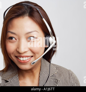 Close-up of a businesswoman wearing a headset and smiling - Stock Photo