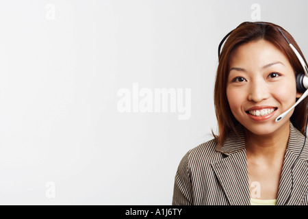 Portrait of a businesswoman wearing a headset and smiling - Stock Photo