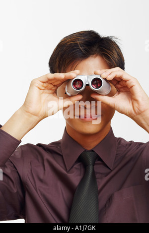 Close-up of a businessman looking through a pair of binoculars - Stock Photo