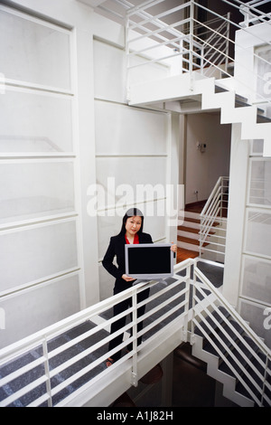 Portrait of a businesswoman showing a growth chart - Stock Photo
