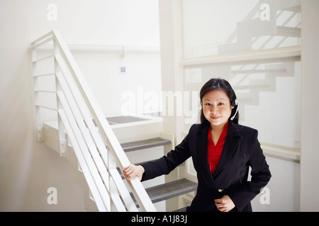 Portrait of a female customer service representative wearing a headset and smiling - Stock Photo