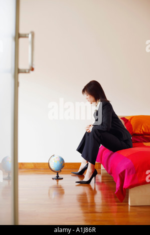 Side profile of a businesswoman sitting on the bed and looking at a globe - Stock Photo