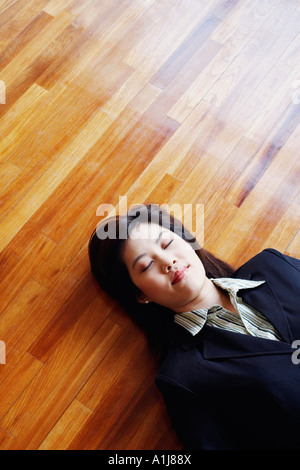 High angle view of a businesswoman lying on the hardwood floor with her eyes closed - Stock Photo