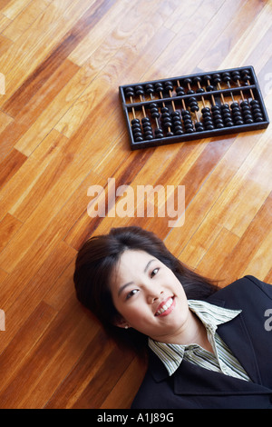 High angle view of a businesswoman lying on the hardwood floor and smiling - Stock Photo