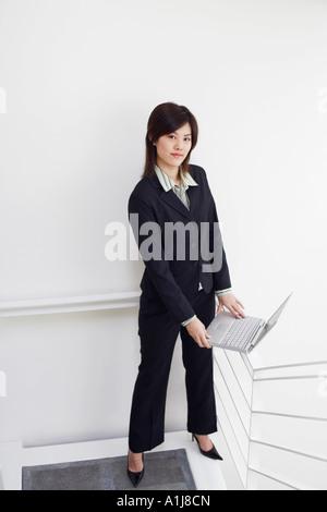 Portrait of a businesswoman holding a laptop - Stock Photo