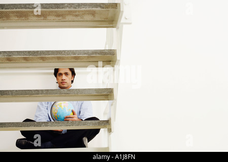 Portrait of a businessman sitting cross-legged on a step and holding a globe - Stock Photo
