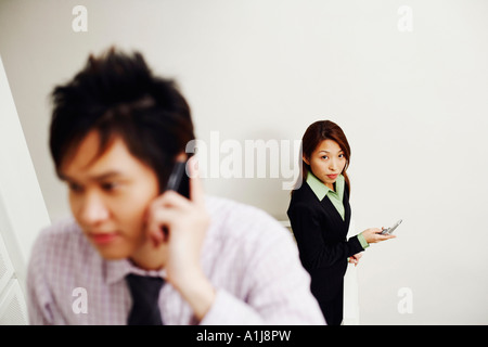 Close-up of a businessman talking on a mobile phone with a businesswoman standing in the background - Stock Photo