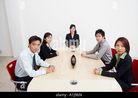 Portrait of business executives sitting in a board room - Stock Photo