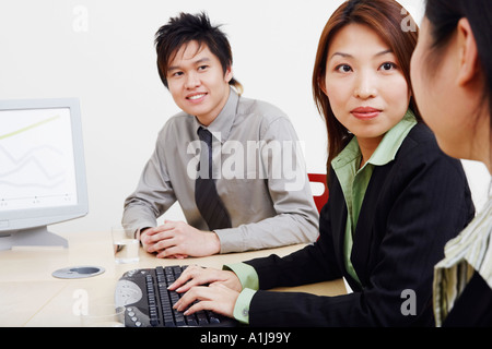 Close-up of business executives looking at each other and smiling - Stock Photo