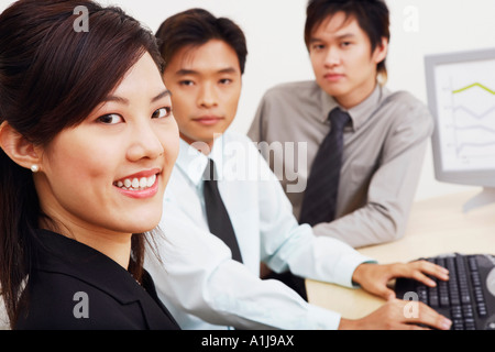 Portrait of a businesswoman sitting with two businessmen in an office and smiling - Stock Photo