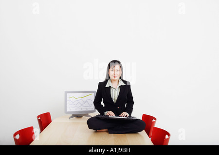 Portrait of a businessman sitting cross-legged on a table with a keyboard and smiling - Stock Photo