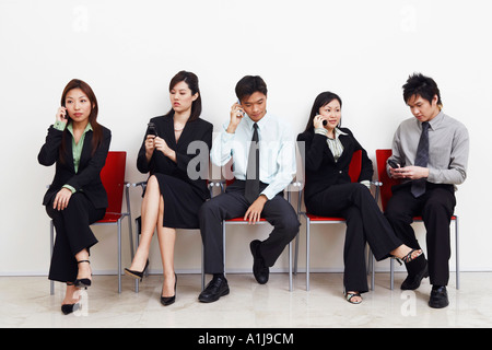 Two businessmen and three businesswomen sitting with mobile phones - Stock Photo