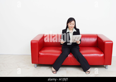 Businesswoman sitting on a couch holding a newspaper and a mobile phone - Stock Photo