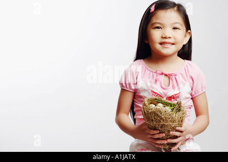 Portrait of a girl holding eggs in a bird's nest - Stock Photo