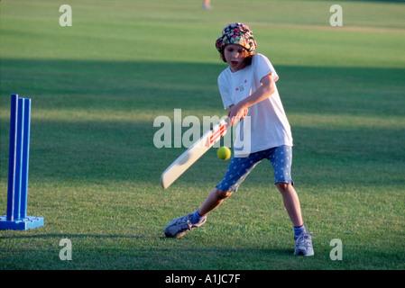 nine year old girl plays cricket on summer evening nr London UK - Stock Photo