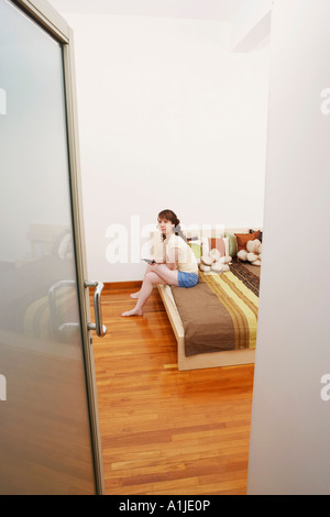 Portrait of a young woman sitting on the bed and holding a mobile phone - Stock Photo