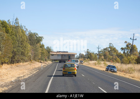 An old wooden house being moved on the road by truck to a new location This is the Warrego Highway in Queensland - Stock Photo
