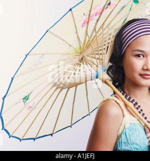 Portrait of a young woman holding a parasol and smiling - Stock Photo