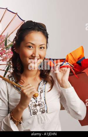 Portrait of a young woman holding shopping bags and smiling - Stock Photo