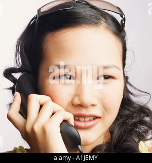 Close-up of a young woman on the phone and looking sideways - Stock Photo
