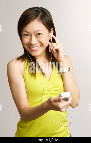 Portrait of a young woman holding a mobile phone and listening to music - Stock Photo