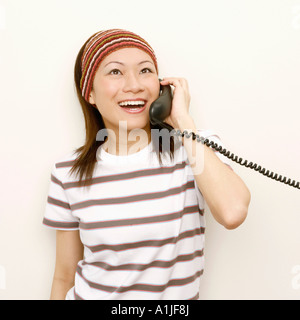 Close-up of a young woman talking on the telephone and looking cheerful - Stock Photo