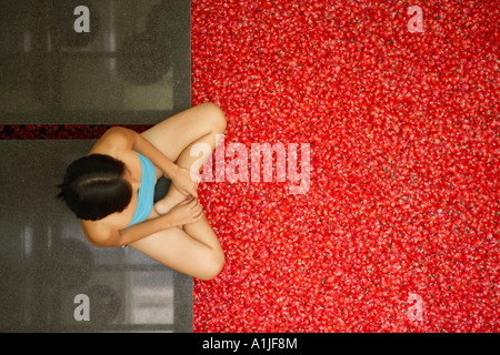 High angle view of a young woman sitting near a hot tub filled with rose petals - Stock Photo
