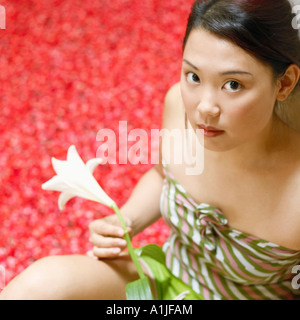 High angle view of a young woman holding a flower and sitting near a hot tub filled with rose petals - Stock Photo