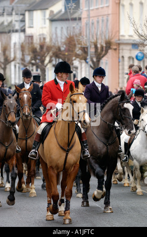 Huntsman in red coat on horseback with followers gather for fox hunt meeting in UK - Stock Photo