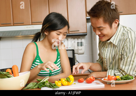 Close-up of a young couple looking at sliced vegetables on a cutting board at a kitchen counter - Stock Photo