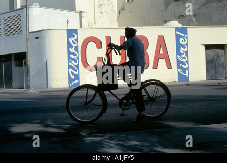 Havana Cuba Man on a bicycle with revolutionary slogans in background - Stock Photo