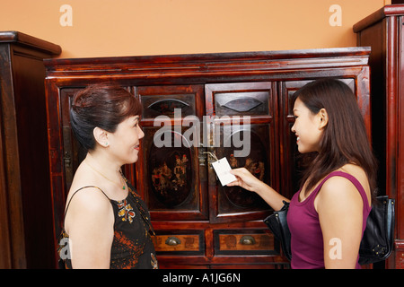 Side profile of a mature woman with her daughter smiling in font of an almirah - Stock Photo