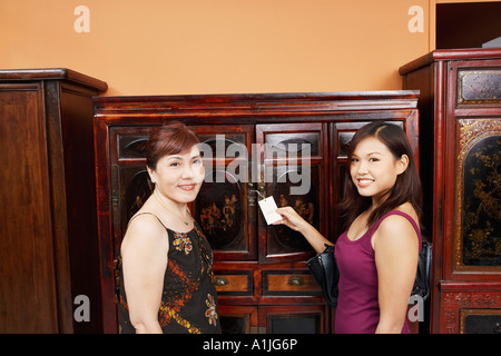 Portrait of a mature woman and her daughter smiling in front of an almirah - Stock Photo
