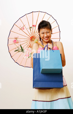 Portrait of a young woman holding a parasol and shopping bags - Stock Photo