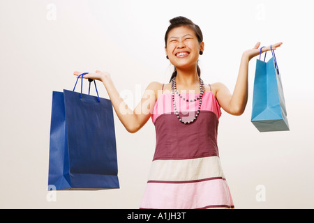 Young woman holding shopping bags with her eyes closed - Stock Photo