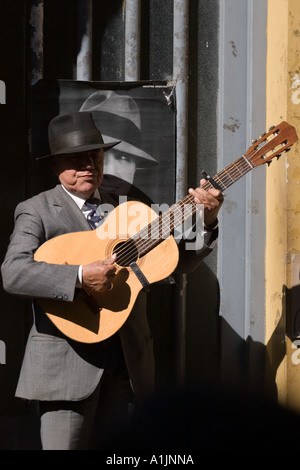 Old man  performing with guitar on sidewalk (in front of picture of Carlos Gardel) B - Stock Photo