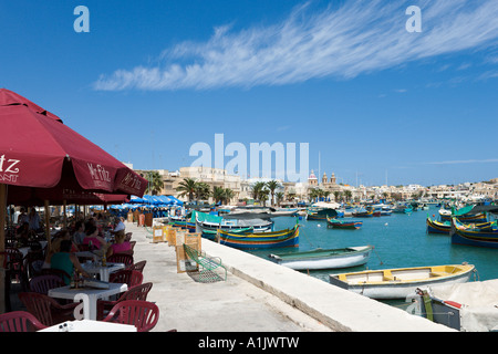 Seafront cafe by the harbour in Marsaxlokk, Malta - Stock Photo