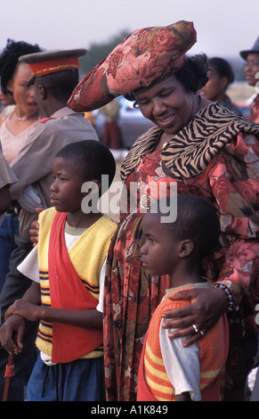 Herero woman wearing traditional dress with her children at the Ma Herero Day Parade August Okahandja Namibia - Stock Photo