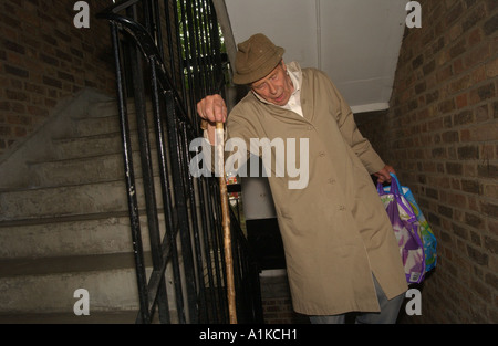Elderly man carrying shopping bags in a stairwell on a housing estate in London - Stock Photo