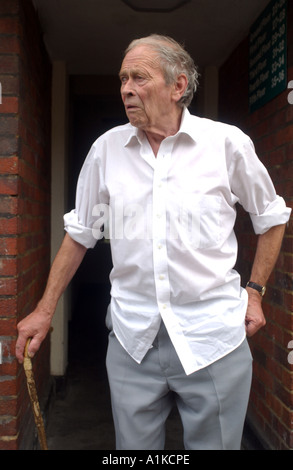 Elderly man leaving home on a housing estate in the East End of London - Stock Photo
