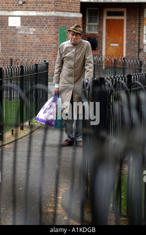 Elderly man carrying shopping and walking home on housing estate in East London - Stock Photo