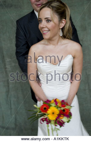 Front view of a bride holding flower bouquet - Stock Photo